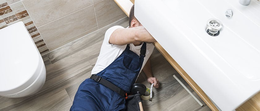 plumber man fixingleaking sink - Priority Plumbing Company